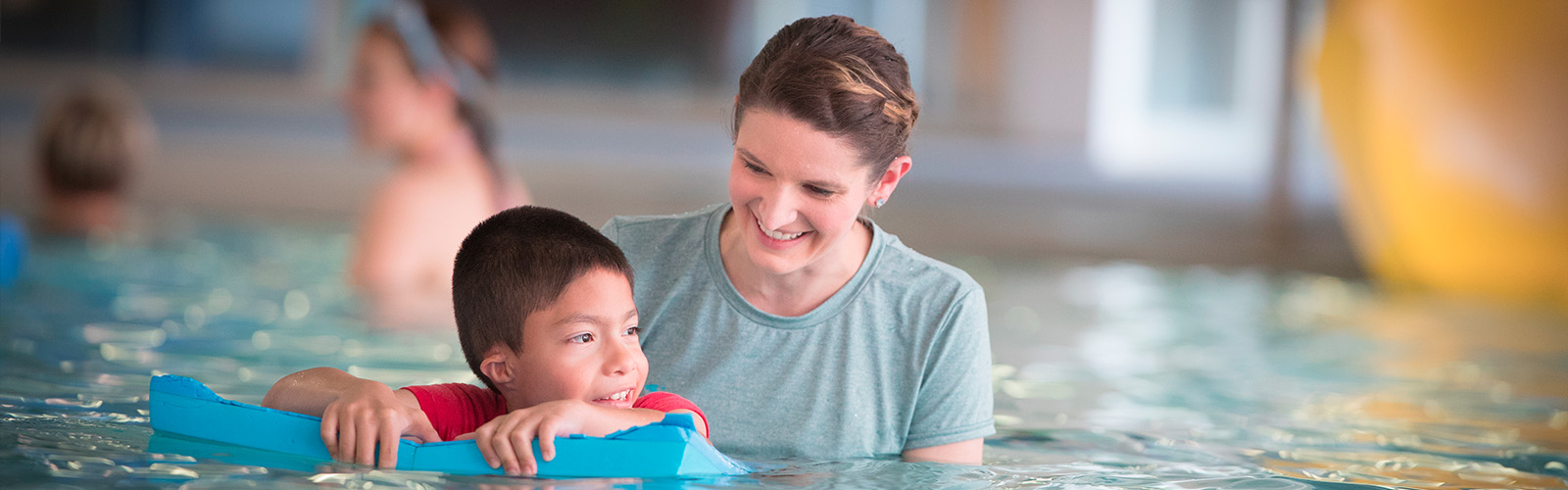 Student working with child in pool
